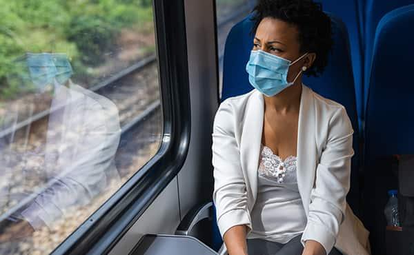 woman on train wearing a mask
